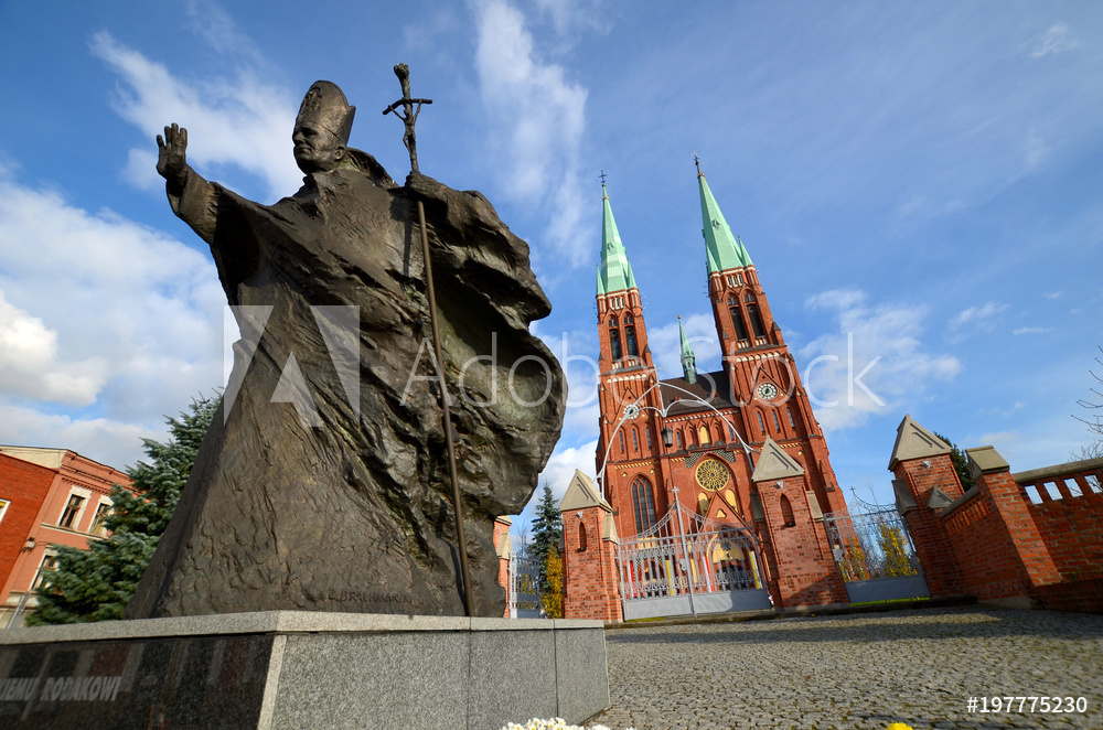 Statue of John Paul II against the background of the cathedral (Rybnik, Poland)
