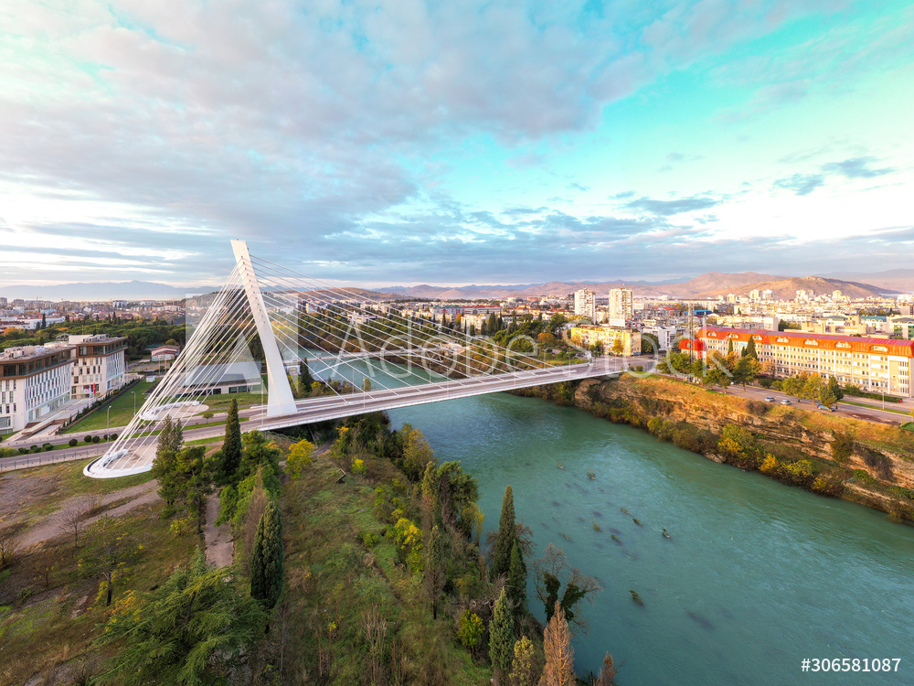 Podgorica, Montenegro: aerial view of the city featuring Millennium bridge and Moraca river in the morning, at sunrise, under beautiful sky. Cable stayed bridge with green area in the foreground.