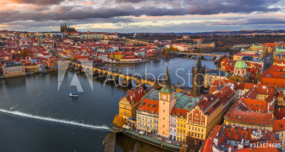 Prague, Czech Republic - Aerial panoramic drone view of the world famous Charles Bridge (Karluv most) and St. Francis Of Assisi Church with a beautiful winter sunset. St. Vitus Cathedral at background