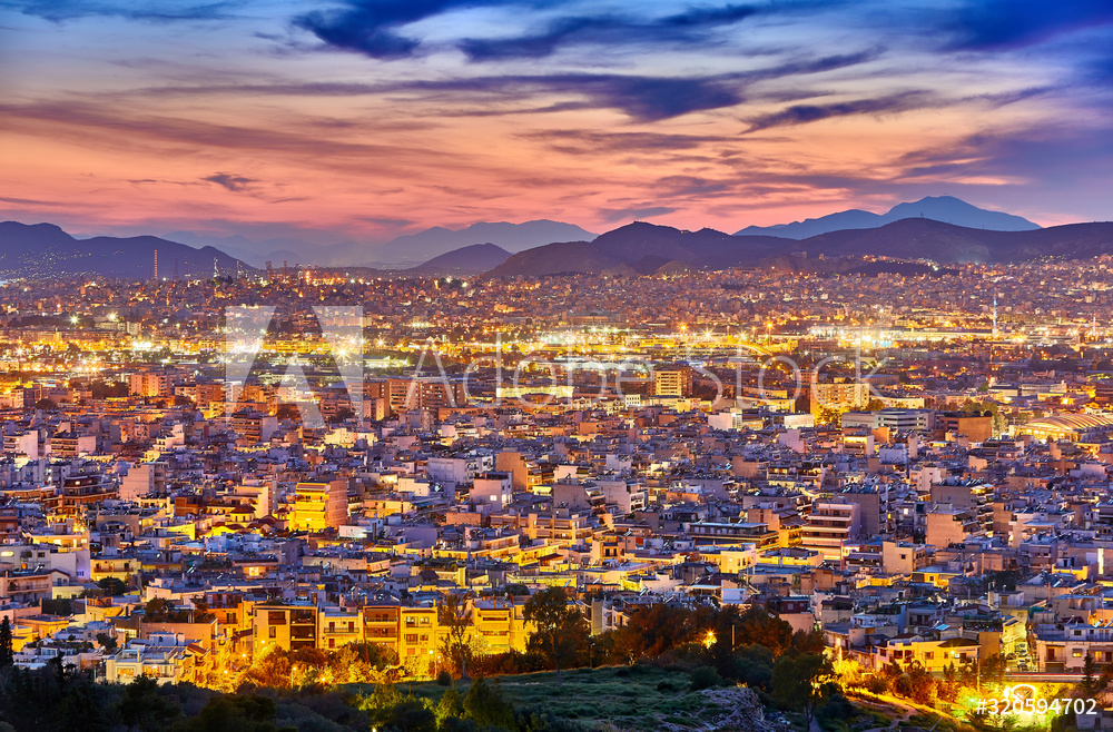 An evening cityscape of many buildings of Athens City, Greece. View from Filopappou Hill or Hill of the Muses. Colorful spring landscape. Urban skyscraper skyline rooftop view at night.